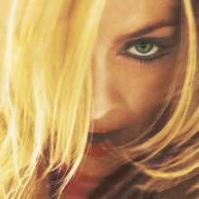 Close-up image of Madonna looking to her front and with her opened mouth. She is wearing mascara in her green eyes and her blonde hair hides part of her face.