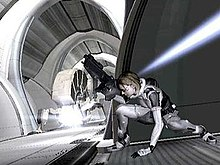 A horizontally rectangular video game screenshot that is a digital representation of a space station. A woman in a white and grey suit holding a large black gun ducks underneath a blue beam of light.