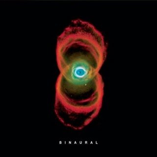 "In a black background is the image of a nebula, which resembles two orange rings of smoke, with an eye-like structure in their intersection. Below it is the title ""BINAURAL"" in white letters."