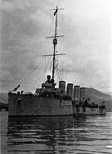 A cruiser sits motionless in the water, with four large funnels, a bridge, and a main mast prominently appearing aboard the ship. A small board lies next to the ship in the foreground, while hills lie in the background.