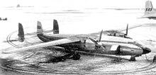 Photograph of two-engine turboprop aircraft with three vertical stabilisers parked on snow-covered ramp.