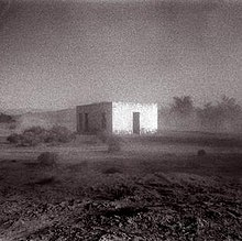 A blurred black-and-white photo of a building in the middle of a desert.