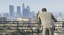 The player character with their back to the camera, and the sprawl of an urban city centre in front of them.