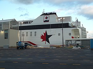 "HSC Virgen de Coromoto - The rear portion of the ""Spirit of Ontario I"" sporting its old maple leaf and star logo. In the foreground is the Port of Rochester under construction."