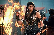 Xena, clad in leather armour accented and decorated in bronze detailing, standing in the middle of a battlefield, flames behind her as she holds her chakram in readiness for battle.