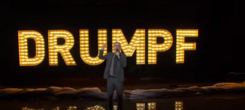 "Comedian John Oliver atop a stage, wearing a suit and holding a microphone; in the background is the text ""Drumpf"""
