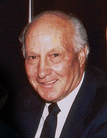 A balding older man, smiling, wearing a suit jacket and tie