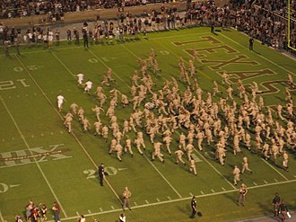Aggie Yell Leaders - Freshmen (in khaki) from the Corps of Cadets chase down and tackle the Yell Leaders (in white) after a victory