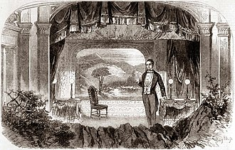 White, middle aged man in 19th-century evening clothes on a small stage with a countryside scene as the backdrop