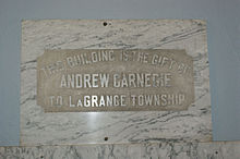 An image of the marble plaque stating that the building was a gift from Andrew Carnegie to Lagrange Township for a free library.