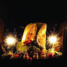 A large plate of food flanked by sparklers
