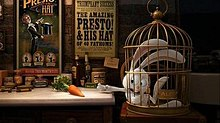 Film screenshot of a rabbit in a cage desperately reaching for a carrot sitting on a nearby table. The table has various jars on it, and posters for the magic show can be seen on the wall in the background.
