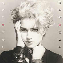 Madonna's image with her right hand placed on her right cheek and with the left hand, she holds on to a number of chains wound on her neck.