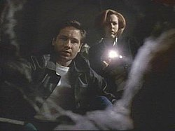 A man in a leather jacket and a woman with a flashlight look into a hole that contains a corpse.