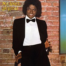 "A smiling adult African American male (Michael Jackson) with a black afro, wearing a black tuxedo, white shirt, and a black bow tie. Both of his thumbs are hooked into his pants pockets with his palms and fingers facing forward and splayed out. The sides of his jacket are tucked behind his hands as he leans back slightly, giving a playful, casual touch to his formal look. Behind him there is a brown brick wall and to the side of his head are ""MICHAEL JACKSON"" in yellow chalk writing and ""OFF THE WALL"" in white chalk writing. ""JACKSON"" and ""WALL"" are separately underlined."
