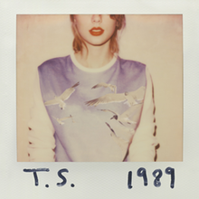 "A polaroid of Swift with shoulder-length blonde hair wearing red lipstick and a long-sleeved sweater with a picture of birds in the sky. Her face is cut off by the frame above the nose and ""T. S."" and ""1989"" are written on the white polaroid frame with black marker."