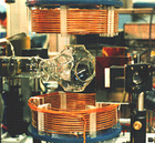 In the MOT, a magnetic field is created by the copper solenoids. Neutral francium atoms enter the glass bulb from the left and are trapped by lasers.