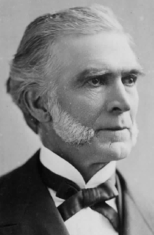 A black and white, head and shoulders photographic portrait of an elderly caucasian gentleman with greying hair and white mutton chop sideburns. He is smartly dressed in a dark suit jacket and white shirt with a Gladstone collar and Kentucky style bowtie.
