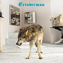 "A gray wolf stands in the middle of a modern bathroom. ""Grinderman"" is written above the wolf in blue gothic text."