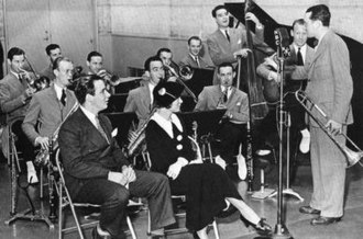 The Dorsey Brothers - Dorsey Brothers Orchestra in the studio, 1934: Pictured are (Back row, l-r): Don Mattison, trombone; Ray McKinley, drums; George Thow, trumpet; Glenn Miller, trombone; Bobby Van Epps, piano. (Middle row, l-r): Skeets Herfurt, tenor sax; Jack Stacy, tenor sax; Jimmy Dorsey, alto sax; Delmar Kaplan, bass; Roc Hillman, guitar; Tommy Dorsey, trombone. Seated in front are band vocalists Bob Crosby and Kay Weber.