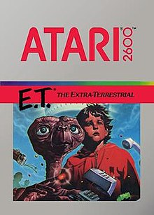 "Artwork of a grey, vertical rectangular box. The top half reads ""Atari 2600. E.T.* The Extra-Terrestrial"". The bottom half displays a drawn image of a brown alien with a large head and long neck beside a young boy in a red, hooded jacket."