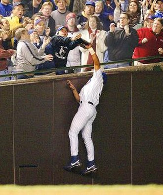 Steve Bartman incident - Fan Steve Bartman and Moises Alou both attempt to catch the foul ball hit by Luis Castillo during Game 6 of the 2003 NLCS at Wrigley Field in Chicago.