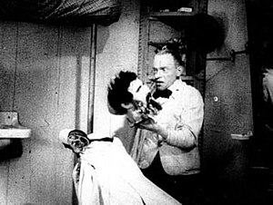 Karl Valentin -  Karl Valentin as the Barber in Mysteries of a Barbershop, 1923, holding the head of a patron (Kurt Horwitz) he has accidentally shaved too close.