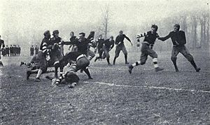 A group of men are playing football. One man is carrying a football, and several others are in his immediate surroundings; six or seven other men are running toward him. A small group of onlookers are watching in the background.