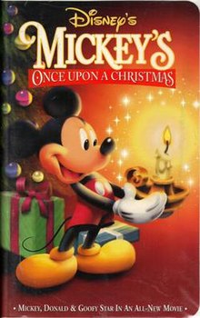 A short anthropomorphic male mouse standing at the left side of the image is holding a candle holder with a brightly burning candle, positioned on the right side of the image, with both of his hands. The mouse is wearing red shorts with white buttons and yellow shoes and is happily smiling. In the background on the left side of the picture stands a decorated Christmas tree with colorfully wrapped gifts lying under it. The video cover includes the film and company's title.
