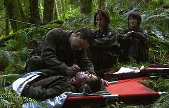 "Valley of Darkness - Chief Tyrol (Aaron Douglas) euthanizes Socinus (Alonso Oyarzun) as Seelix (Jennifer Halley) and Cally (Nicki Clyne) look on. This scene was controversial during production. Douglas described filming such scenes as ""very draining"" emotionally."