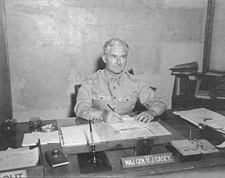 "A name plaque reads: ""Maj. Gen. Hugh J. Casey"". The wall behind him is covered in huge map of New Guinea."