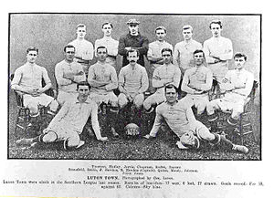 "An association football team. Six men stand across the back, the third from the left of which is wearing a dark shirt and a cap. In front of them sits a row of seven men on chairs, with a mustachioed gentleman with hair that is quite long for the time sitting in the middle. Finally, two men recline on the floor in front of them, one on either side of a football marked ""LTFC 1909–10""."