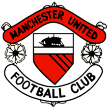 "A football crest. In the centre is a shield with a ship in full sail above a red field with three diagonal black lines. Either side of the shield are two stylised roses, separating two scrolls, the upper scroll is red and reads ""Manchester United"" in black type, while the lower scroll is white with ""Football Club"" also written in black."