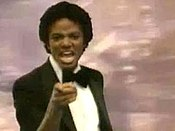 A adult African American male with short black hair. He is pointing forward with his right hand and is making a facial expression and he is wearing a black bow tie with a black and white tuxedo. Behind him, there is a pink background.