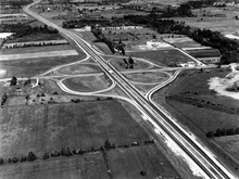 A black-and-white photo of a cloverleaf interchange between a freeway and surface road surrounded by farmland and trees