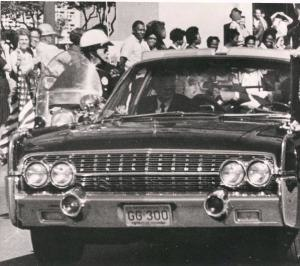 Assassination of John F. Kennedy - Ike Altgens' photo of the Presidential limousine taken between the first and second shots that hit President Kennedy. Kennedy's left hand is in front of his throat and Mrs. Kennedy's left hand is holding his arm.