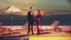 Calvin Harris holding a martini for Dua Lipa on a pool deck. Harris wears a suit and Lipa wears a purple outfit.