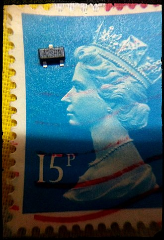 Surface-mount technology - A MOSFET transistor, placed upon a British postage stamp for size comparison