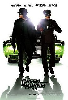 Two suited masked men, behind them is a large car behind them with green headlights, the film's title ,credits and release date below them while the cast names above.