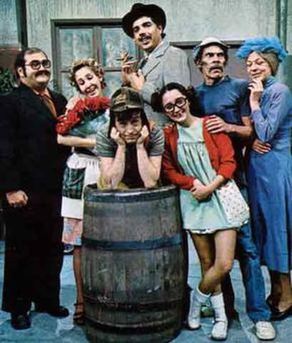 El Chavo del Ocho - The cast of the series photograph themselves for a picture in 1979, just after Carlos Villagrán (Quico) left the show. Chespirito is leaning on Chavo's trademark barrel at the center of the picture.