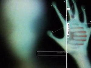 "Inexplicable, yet a Fact - A frame from the opening sequence showcasing the response of the graphic designer of the series Inexplicable, yet a Fact to the famous X-Files punchline, ""The Truth is Out There."" The artist's depiction of a blurred six-fingered grey alien's head and hand, with the blurred Inexplicable, yet a Fact logo on its palm, is accompanied with the caption ""Alien image 321b/3"" (in black) and the grammatically-incorrect subcaption ""ALIENS IS OVER THERE"" (in white): another piece of evidence to the claim that the information presented by the series is underverified."