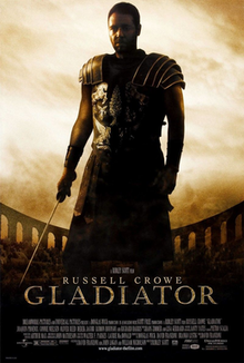 A man standing at the center of the image is wearing armor and is holding a sword in his right hand. In the background is the top of the Colosseum with a barely visible crowd standing in it. The poster includes the film's title and credits.