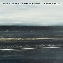 "A mostly charcoal grey, lightly blue painting of coal mountains backdropped against a overcast sky. The words ""Public Service Broadcasting"" and ""Every Valley"" are written in bold black font on the top left and top right corners of the image, respectively. It is titled ""Viaduct', and was painted by Hannah Benkwitz."