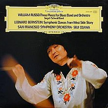 Photo of Seiji Ozawa, wearing a flowered white shirt, and conducting an orchestra