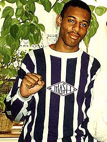 Photograph of a young Afro-Caribbean male, cropped to show his chest and head. He has black hair, shaved very short, and a slight moustache. He is wearing a navy-and-white vertically striped crew neck shirt. He is standing in front of a large indoor plant.