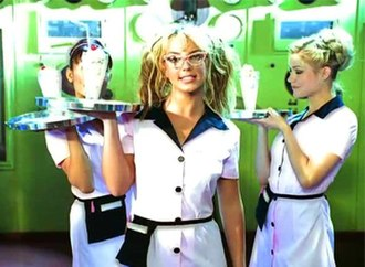 "(You Drive Me) Crazy - Spears dressed as the waitress of a dance club in the music video for ""(You Drive Me) Crazy"". To her right is actress Melissa Joan Hart."