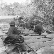 Two soldiers manning a machine-gun in a heavily sandbagged pit observe the perimetre of their defensive position through the vegetation.