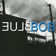 "A black-and-white silhouette image of an industrial factory. Large volumes of smoke are visible in the sky. Uppercase white mirrored text in the center reads ""Blue"" (stylized as ""ƎU⅃ᗺ""); uppercase blue text next to it reads ""Bob"", with black outline around the text."