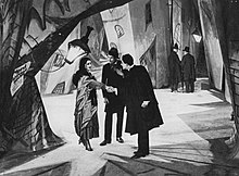 A black-and-white film still. Three figures stand facing each other on a heavily stylized street set.