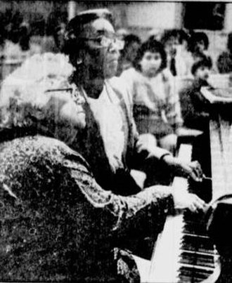 Ebony and Ivory (piano duo) - Ruth Eisenberg and Margaret Patrick playing piano, using one hand each.
